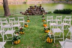 婚礼装饰用秋天南瓜和花 仪式室外在公园 客人的白色椅子 免版税库存图片