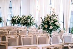 婚礼装饰,辅助部件,兰花,玫瑰,玉树,花束在餐馆,主持桌设置 库存图片