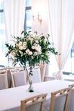 婚礼装饰,辅助部件,兰花,玫瑰,玉树,花束在餐馆,主持桌设置 免版税库存照片