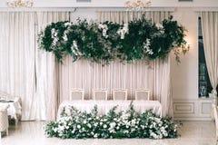 婚礼装饰,辅助部件,兰花,玫瑰,玉树,花束在餐馆,主持桌设置 免版税库存图片