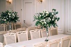 婚礼装饰,辅助部件,兰花,玫瑰,玉树,花束在餐馆,主持桌设置 库存照片