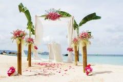 婚礼设定了和在热带海滩背景的花 免版税库存照片