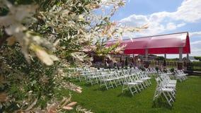 婚礼走道装饰 婚姻白色的椅子 婚姻的仪式户外 在庭院里设定的婚礼 晴朗的日 股票视频