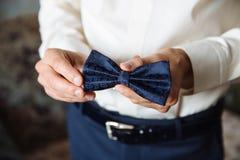 婚礼辅助部件 蝶形领结在新郎的手上 免版税库存照片