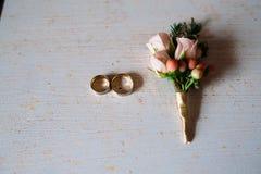 婚礼辅助部件 钮扣眼上插的花,金黄圆环,花美丽的花束在白色织地不很细桌上的 新娘的概念 库存图片