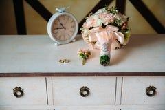 婚礼辅助部件 钮扣眼上插的花,金黄圆环,花美丽的花束在白色织地不很细桌上的 新娘的概念 库存照片