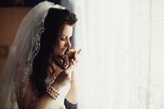 婚礼钮扣眼上插的花在新娘的手上 免版税库存图片