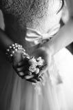 婚礼钮扣眼上插的花在新娘的手上 库存图片