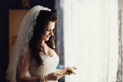 婚礼钮扣眼上插的花在迷人的新娘的手上 免版税库存图片