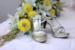 婚礼鞋子和白色黄色花婚礼花束  库存图片