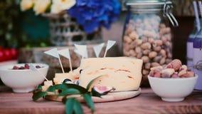 婚礼食物酒吧特写镜头视图  夏天婚礼快餐桌 花、乳酪、坚果、无花果和饮料 股票录像