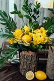婚礼黄色黄水仙、绿叶和柠檬的花的布置在树桩,特写镜头 免版税库存图片