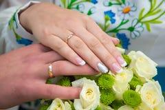 婚礼,新娘有婚戒的` s手在婚礼花束 免版税图库摄影
