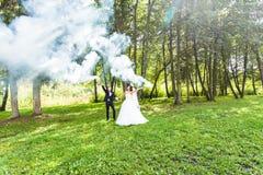 婚礼,爱,关系,婚姻 微笑的新娘和新郎与蓝色烟 免版税库存图片