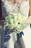 婚纱和白玫瑰新娘花束  垂直的照片 库存图片