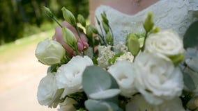 婚纱的美丽的年轻新娘有花的在一个晴朗的公园 影视素材