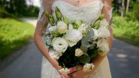婚纱的美丽的年轻新娘有花的在手上今后在一个晴朗的公园进来 股票视频