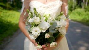 婚纱看看的美丽的年轻与他的新娘花在手上和戏剧在一个晴朗的公园 股票视频