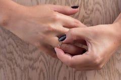 离婚,分离:去除婚礼或定婚戒指,舱内甲板位置的妇女, 免版税库存图片