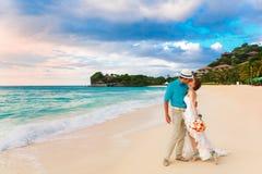婚姻。亲吻在热带海岸的Bbride和新郎在sunse 免版税库存照片