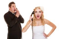 婚姻。恼怒的新娘和新郎谈话在电话 免版税库存图片