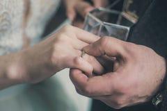 婚姻交换圆环,把圆环放在手指上 图库摄影