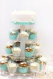 婚宴喜饼和杯形蛋糕在褐色和奶油在蓝色,白色和 库存照片