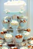 婚宴喜饼和杯形蛋糕在褐色和奶油在蓝色,白色和 图库摄影