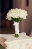 婚姻在一张白色桌上的白玫瑰花束 免版税库存照片