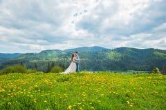 婚姻在山,在爱,山背景,站立的被围拢的蒲公英的一对夫妇,在有绿草的草坪中, 库存图片