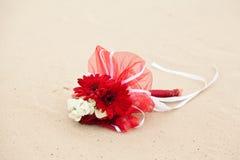 婚姻在沙子的红色和白花花束 免版税库存图片