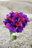 婚姻在海滩的紫色和红色花花束 库存照片