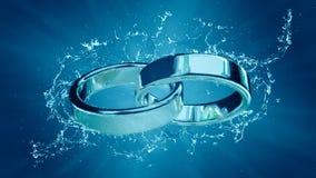 婚姻婚姻与圆环圆环婚戒结婚在水飞溅下 库存照片