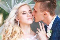 婚姻 新娘和新郎,亲吻在一个美丽的公园在婚礼之日 浪漫已婚夫妇 户外婚姻的夫妇是拥抱 免版税库存照片