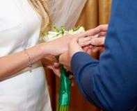 婚姻白色的背景明亮的环形 新郎和他可爱的妻子的手 库存图片