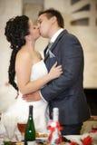 婚姻的亲吻愉快的新郎和新娘 免版税库存图片
