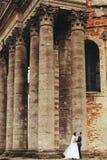 婚姻的夫妇在一个老大教堂的前面站立 库存照片