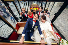 婚姻的夫妇微笑坐与旅游火车的朋友 免版税图库摄影