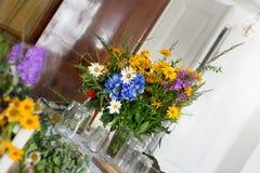 婚姻的庆祝的五颜六色的野花花束装饰户内 免版税库存图片