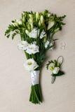 婚姻的新娘花束和钮扣眼上插的花新郎和圆环的 免版税库存图片