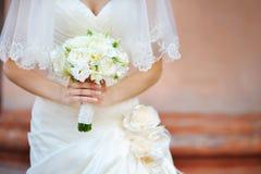 婚姻的新娘花束在象牙颜色的手上 免版税库存图片