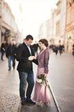 婚姻 美好的夫妇,有桃红色礼服的新娘走在老城市的 库存图片