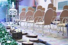 婚姻,圣诞节、椅子、古色古香的白色木灯笼、藤和木头的装饰绊倒与蜡烛 免版税库存照片