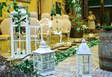 婚姻,圣诞节、椅子、古色古香的白色木灯笼、藤和木头的装饰绊倒与蜡烛 免版税库存图片