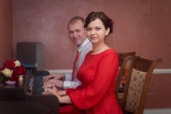 婚姻:新婚佳偶、新娘和新郎,恋人夫妇,弹钢琴 图库摄影
