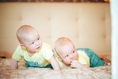 婴儿小儿童双胞胎六个月在家在床上 免版税库存图片