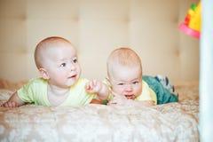 婴儿小儿童双胞胎六个月在家在床上 免版税库存照片