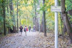 """婴儿推车在一个公园在秋天与仅德国路牌†""""走的步幅 库存照片"""
