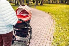 婴儿推车在公园漫步 库存图片