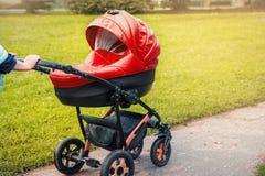 婴儿推车在公园漫步 免版税库存图片